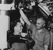 Two men, Petty Officer Edward Carbullido and Captain Edward L. Beach (left to right), standing next to the periscope in the conning tower compartment of the nuclear submarine USS Triton
