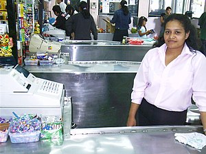 Cashier - A cashier at her register in a Panamanian grocery store.