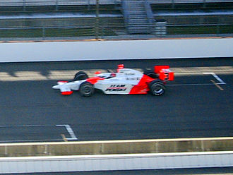 "Indianapolis 500 traditions - Hélio Castroneves makes his pole-winning qualification run in 2007 during ""Happy Hour"". Note the shadows cast on the racing surface."