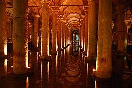 Vue intérieure d'un bâtiment, de l'eau est présente au pied de colonnes