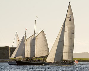 Photograph of Columbia on the right overtaking two other yachts.