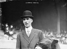A man standing in a baseball stadium wearing a suit and bowler hat. He has a coat folded over his left arm.