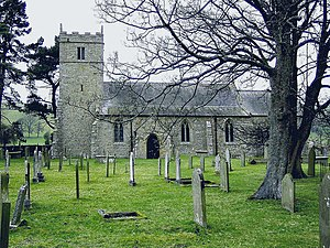 A stone church seen from the south with a battlemented tower on the left