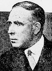 Black and white portrait photo of a white man wearing a jacket and tie