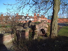 A small arched sandstone bridge seen from an angle, with a tree to the right and houses and factory buildings in the background.
