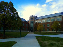 Picture of a three-story building with walkways on an autumn day