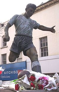 A statue of a man wearing a white shirt and blue shorts, about to kick a football