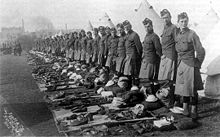 A line of soldiers standing behind tents with their army gear neatly laid out ready to be inspected. The line of soldiers continues into the distance were buildings can be seen the background.
