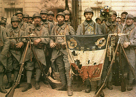 French Poilus posing with their war-torn flag in 1917, during World War I El 114 de infanteria, en Paris, el 14 de julio de 1917, Leon Gimpel.jpg
