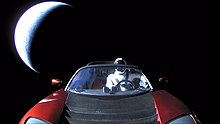 Photograph of the front of a red convertible sports car floating in space. There is a humanoid figure in the driving seat. In the background, partially illuminated in a crescent shape, is planet Earth.