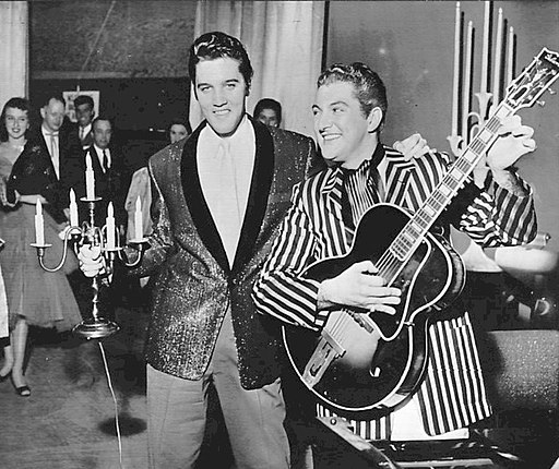Photo of Elvis Presley and Liberace trading places in 1956. The two entertainers switched jackets with Elvis taking Liberace's candelabra and Liberace playing Elvis' guitar for a publicity photo. Both were appearing in Las Vegas.