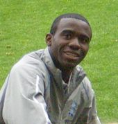 Young black man with close-cropped hair wearing a grey anorak