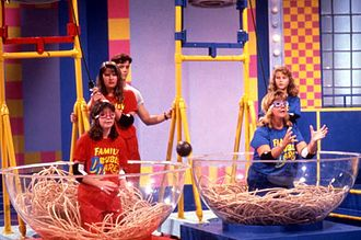 "Double Dare (Nickelodeon game show) - A 1990 Family Double Dare toss-up physical challenge showing two contestants trying to catch a ""meatball"" in a bowl of ""spaghetti."""