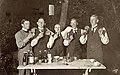 Fem män höjer sina snapsglas ute i en trädgård stående vid ett trädgårdsbord med kaffekoppar och flaskor - Nordiska Museet - NMA.0048890.jpg