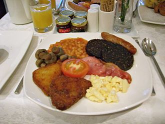 Breakfast - A full English breakfast with scrambled eggs, sausage, black pudding, bacon, mushrooms, baked beans, hash browns, and half a tomato