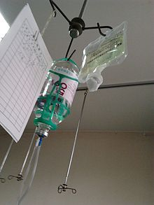 Photograph of two intravenous solution bags (containing glucose and levofloxacin, respectively) and a paper log sheet hanging from a pole.