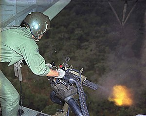Suppressive fire - A rotating-barrel minigun being fired from a gunship in Vietnam during the war.