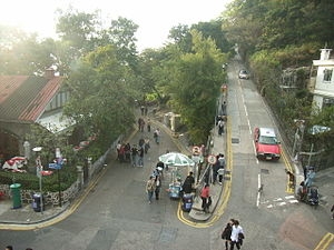 Victoria Gap - The road junction at Victoria Gap, next to the Peak Tower. From left to right: Peak Road, the Peak Lookout Restaurant, Harlech Road (with street vendor), Mount Austin Road (with taxi), Lugard Road.