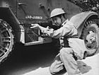Soldier kneels aiming down the iron sight of a Thompson submachine gun in front of a M3 Half-track.