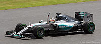 A picture of Lewis Hamilton driving a Mercedes F1 W06 Hybrid formula one car during the 2015 British Grand Prix, raising his arm in celebration after winning the race.