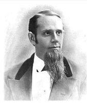 A middle-aged American gentleman of the immediate post-civil-war era. In this black-and-white portrait shot the subject looks to the viewer's right. His hair is short and sharply combed, and a magnificent beard is prominent on his chin. He wears a dark suit and white shirt.