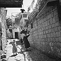 Het dorp Peki'in in Opper Galilea. Vrouw met een mand op het hoofd en twee jonge, Bestanddeelnr 255-3755.jpg