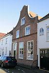 foto van Huis met zadeldak en klokgevel, ingang omlijst door gegroefde pilasters en een kroonlijst