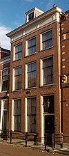 foto van Huis met eenvoudige gevel met rechte kroonlijst voor dwarskap. Stoep met eenvoudig stoephek