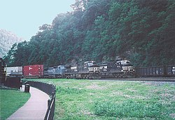 Three trains passing on triple-track mainline of Norfolk Southern Railway at Horseshoe Curve in Logan Township