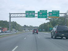 A six-lane highway at an interchange with three green signs over the road. The left sign reads east Interstate 195 to New Jersey Turnpike Interstate 95 Belmar, the middle sign reads exit 1B U.S. Route 206 north White Horse next right, and the right sign reads exit 1A U.S. Route 206 south Bordentown upper right arrow exit only.