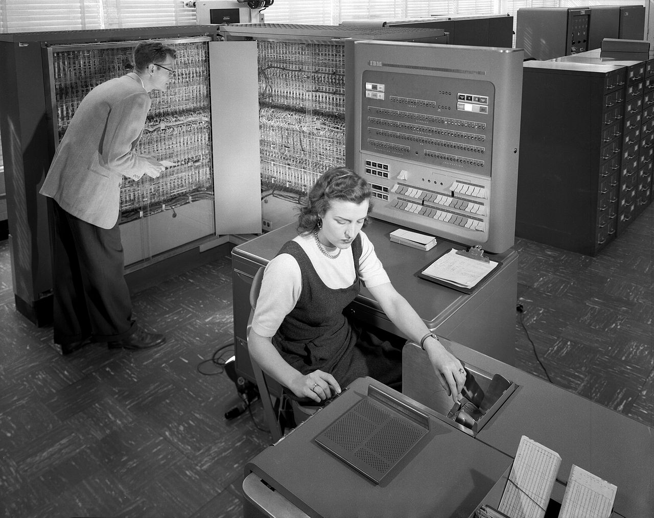 Man and woman using the IBM type 704 electronic data processing machine