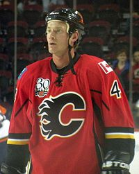 "Hockey player in red uniform, with a large ""C"" in the middle. He looks to his right."