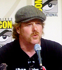 A bearded man wearing a black shirt and a gray beret sits in front a microphone. Sunglasses are han