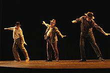 Three men in hats and beige or brown outfits dance on a dark stage