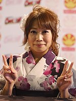 Junko Takeuchi holding two peace signs while smiling