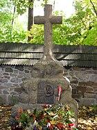 "A stone cross atop a large rock. A plaque mounted on the rock reads: ""Ostaszkow, Starobielsk, Kozielsk, Katyń 1940"", followed by ""Zwiazek Sybrakow""."