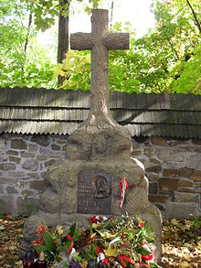 "A stone cross atop a large rock. A plaque mounted on the rock reads: ""Ostaszkow, Starobielsk, Kozielsk, Katyń 1940"", followed by ""Zwiazek Sybrakow""."