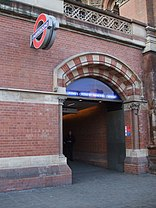 A brick and stone arched entrance with the London Underground roundel sign fixed to the wall alongside.
