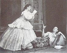 A man with a shaven head, wearing Asian dress, reclines on the floor and gestures at a woman in 19th century dress, who is writing, apparently at the man's dictation.