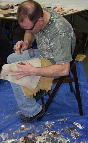Knapping - A man demonstrates flintknapping a stone tool