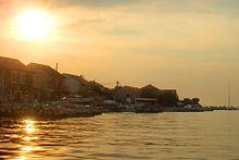 Yukarıdaki gökyüzünde parlak bir güneşin olduğu sahil şeridinin aşağıdaki suya yansıyan ve sahildeki binaları karartan fotoğrafı
