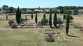 Vestiges au sol, indépendants les uns des autres et de forme rectangulaire, entourés de cyprès et dans un environnement urbain en arrière-plan.