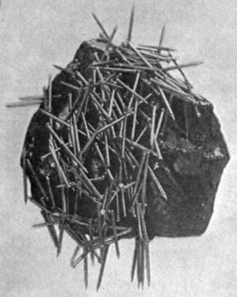 Lodestone, a natural magnet, attracting iron nails. Ancient humans discovered the property of magnetism from lodestone. Lodestone attracting nails.png