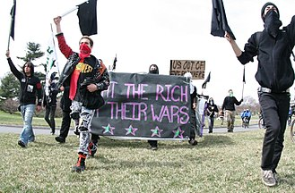 "Protests against the Iraq War - A black bloc group marches as part of an Iraq War protest in Washington, D.C., March 21, 2009. The full text of the banner reads, ""Fight the rich, not their wars."""