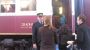 Grapevine, Texas - The conductor assists a passenger as the Grapevine Vintage Railroad stops at the Fort Worth Stockyards.
