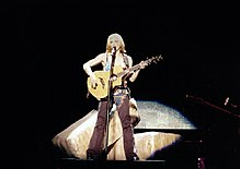 Image of Madonna playing the acoustic guitar during a concert
