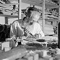 Man maakt thorarollen achter een volle werktafel, Bestanddeelnr 255-2344.jpg