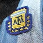 Photographie en couleurs. Gros plan sur l'écusson officiel de la fédération argentine de football cousu sur un maillot bleu ciel et blanc.