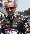 A man in his early thirties wearing black rectangular sunglasses and racing overalls with sponsors logos. He is smiling at the camera