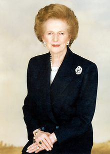Portrait at half length of an older white woman with coiffed, light golden brown hair, wearing jewellery, dressed in a dark suit, hands crossed, against a clear background